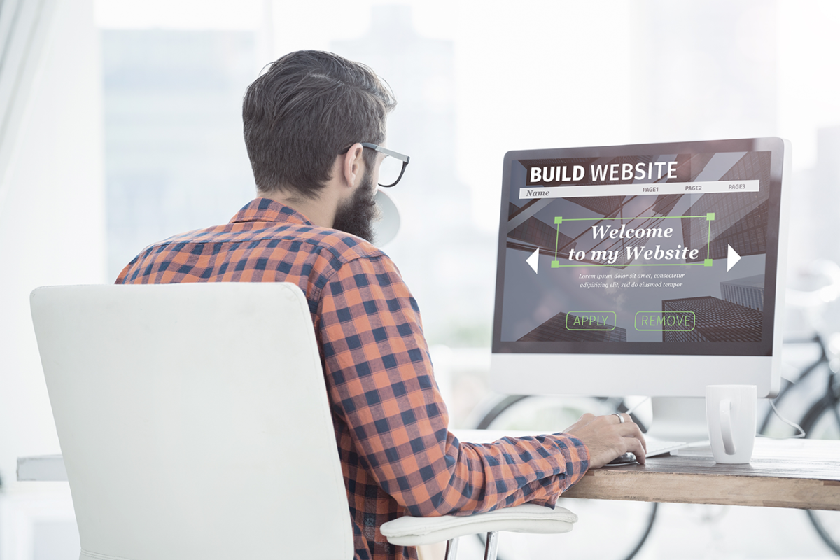 white man on computer building his own website