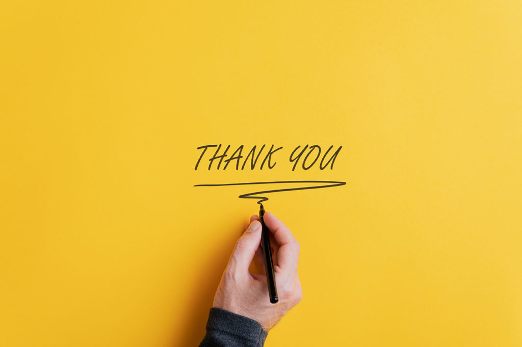 A hand writing thank you on yellow paper