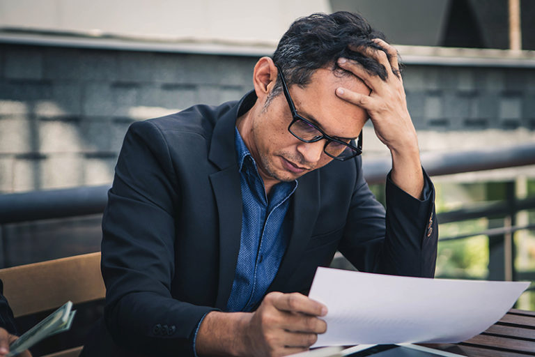 a business owner overwhelmed and burned out looking at an important document