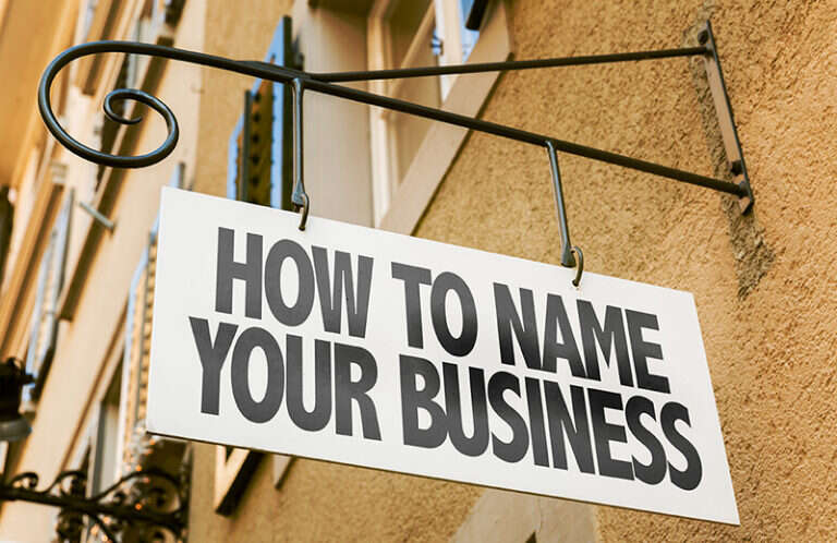 A small business sign hanging outside with the words How to name your business