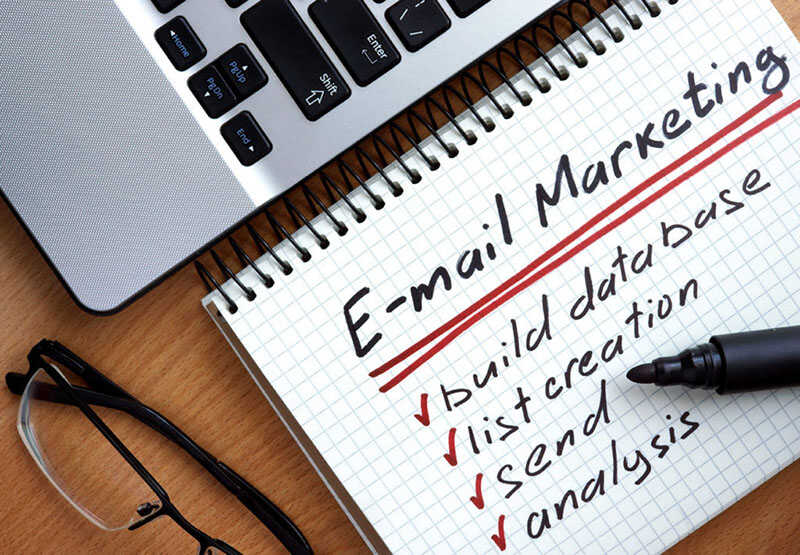 a workstation with a laptop and notepad with email marketing strategies written on it
