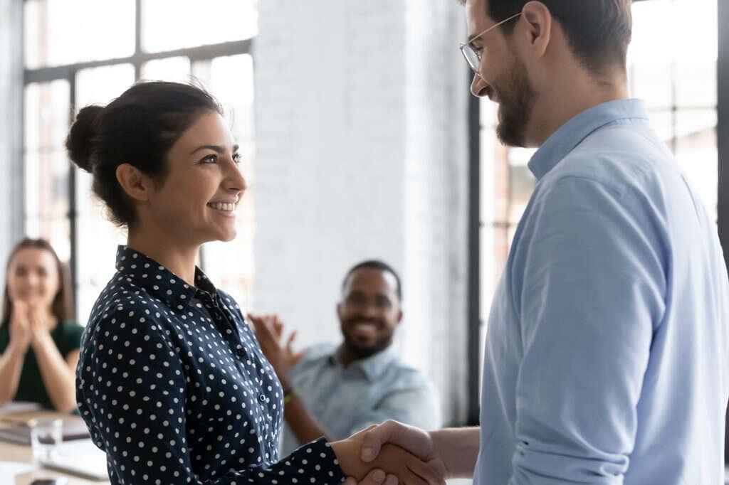 Happy businessman handshake biracial employee greeting with promotion