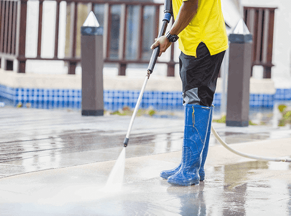 African American man doing power washing outside