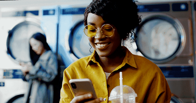 Young black women on her phone in a laundromat.