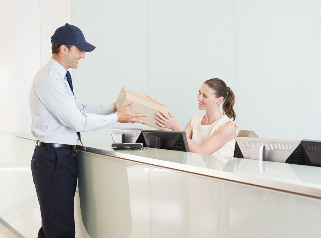 A white delivery man handing a package to a white receptionist in an office