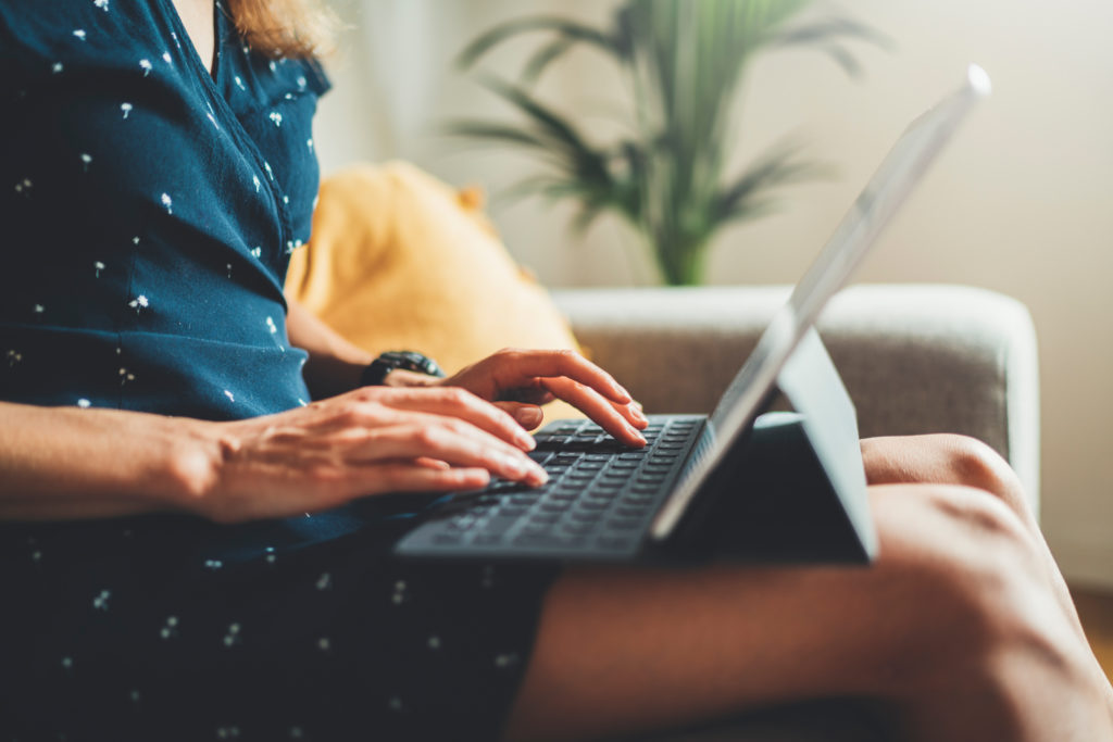 A young female working from home sitting on a sofa with a laptop on her lap