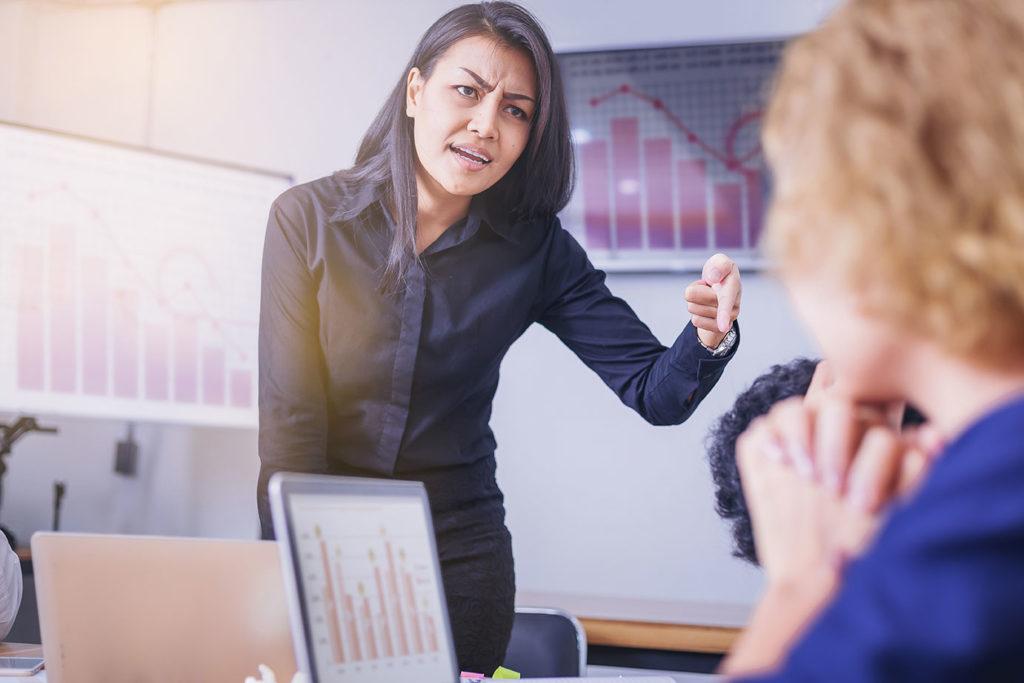 A pretty Asian boss woman scolding an employee in an office