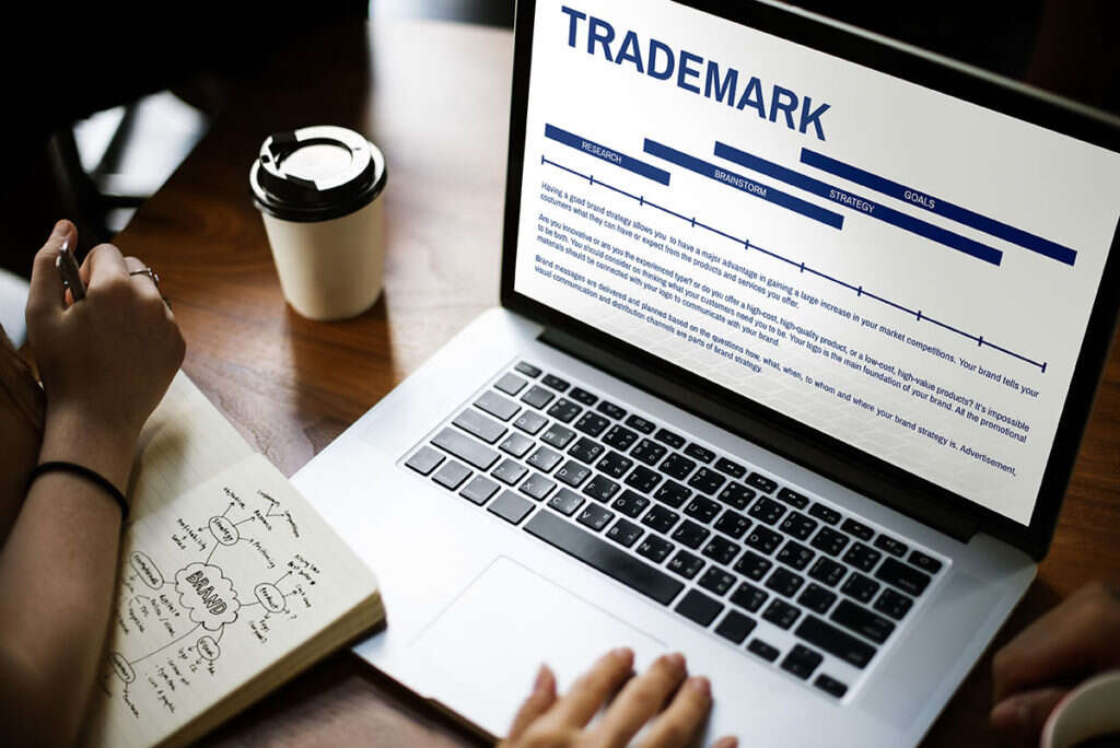 Trademark process on Mac laptop screen with two business owners' hands.