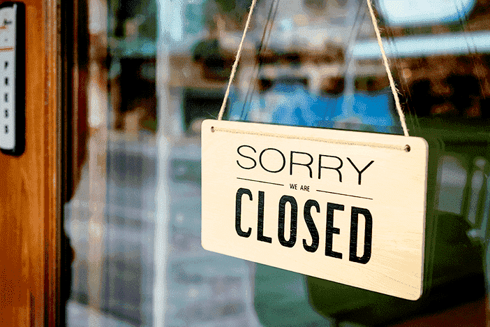 Dissolve an LLC: Sorry We Are Closed sign on small business door.