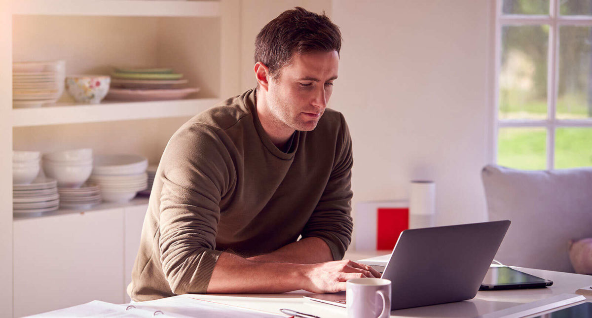 Young white male working remotely from home with his laptop and a cup of coffee