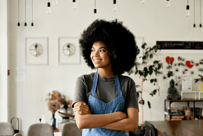 Beautiful black woman with afro in a coffee shop asking herself what is the best way to pay yourself from your LLC