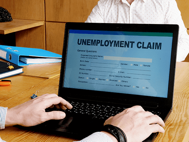 """White business man sitting at a desk filing an unemployment claim, wondering """"can LLC owners collect unemployment?"""""""