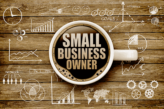 Coffee cup on wooden table with the words Small business owner in the coffee to inspire entrepreneurs to form a DBA vs LLC