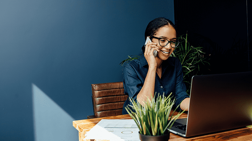 A happy African American freelancer talking on her phone in her office while on her laptop.