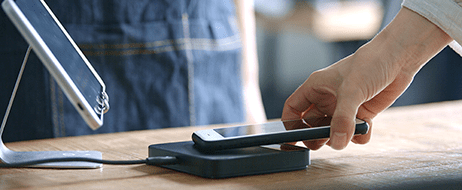 A customer holding his phone to a mobile card reader to pay for a purchase