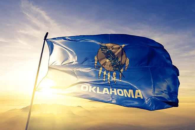 LLC Oklahoma flag flying in front of rising sun.